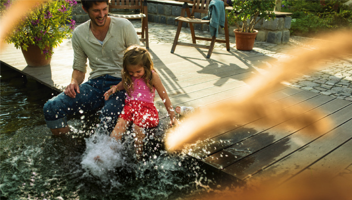 Vater und Kind planschen mit Füßen im Wasser