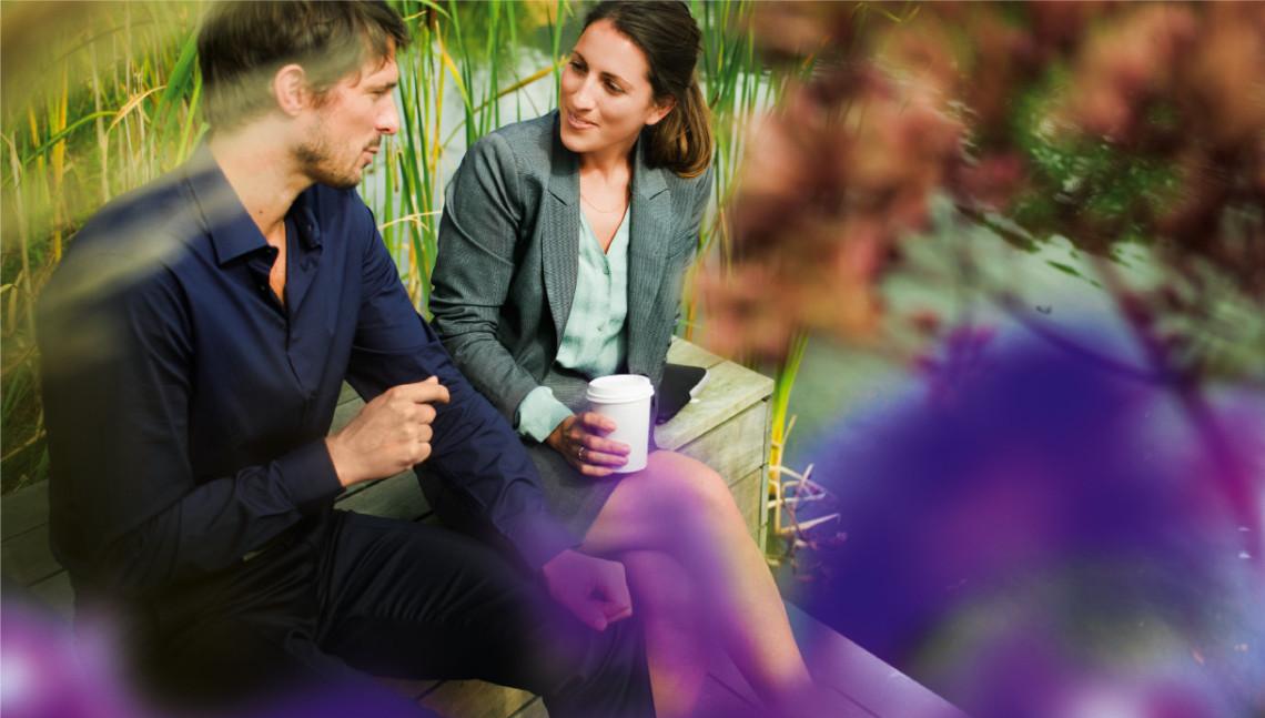 Mann und Frau beim Kaffeetrinken neben einem See