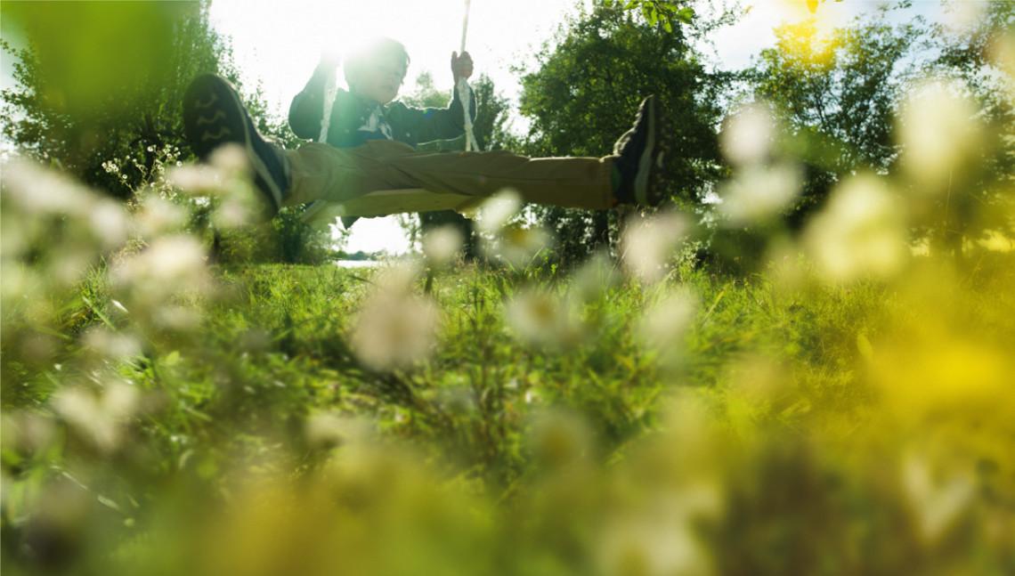 Junge schwingt im Schaukel im Garten