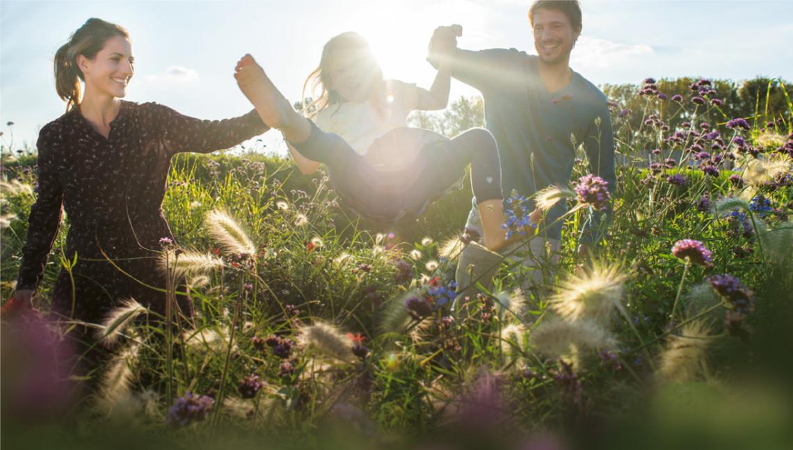 Familie spielt auf Blumenwiese