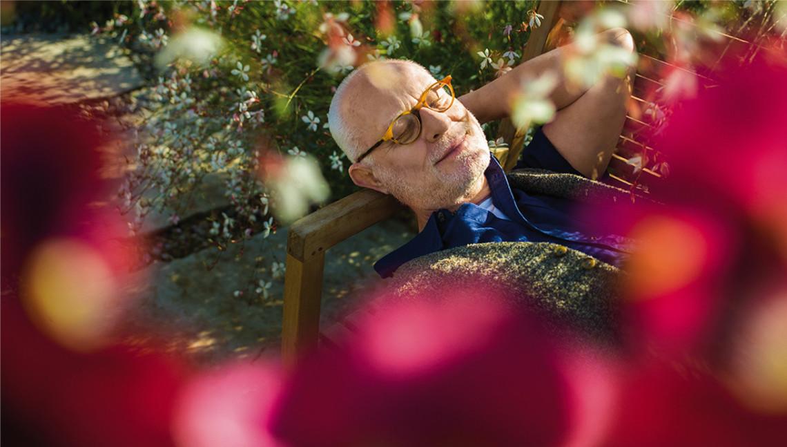 Mann ruht sich auf eine Bank im Garten aus