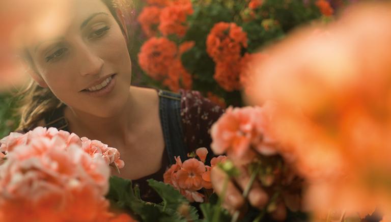 Frau umgeben von Blumen im Garten