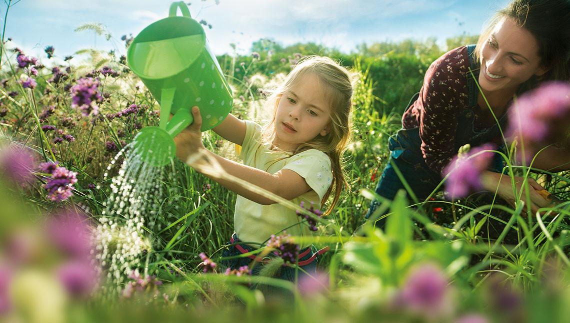 Mutter und Kind begießen Pflanzen im Garten