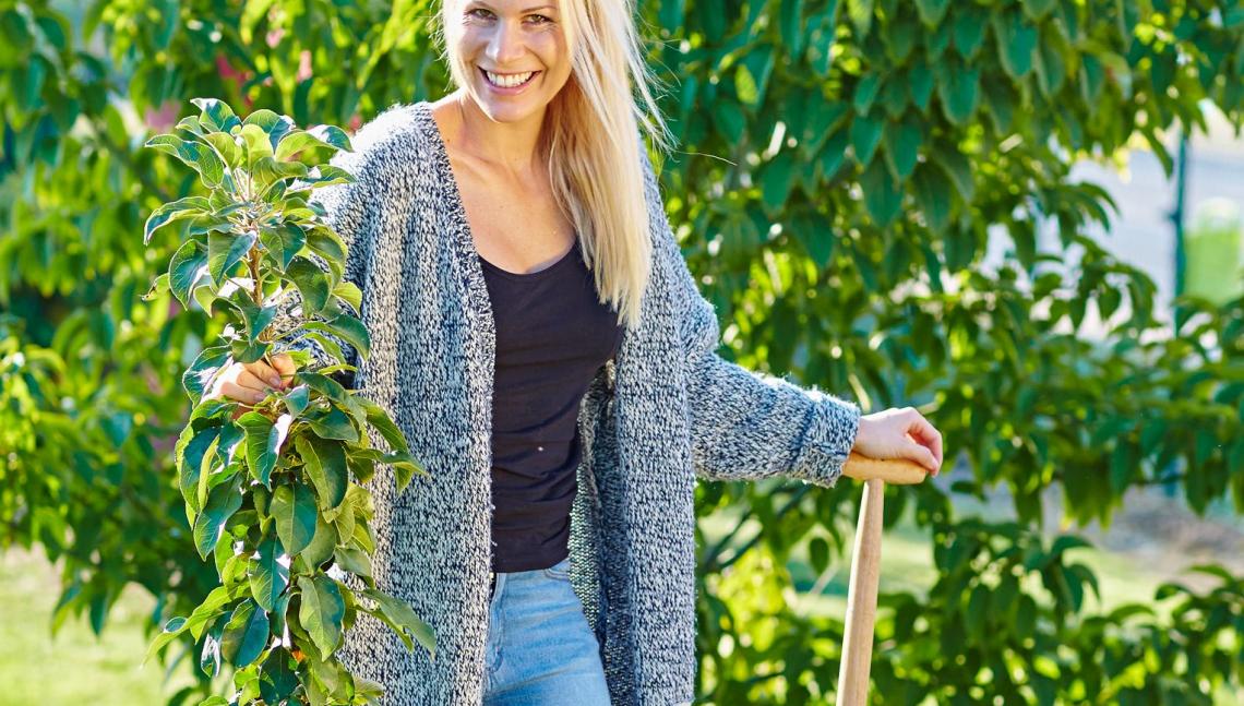 Frau pflanzt Apfelbaum